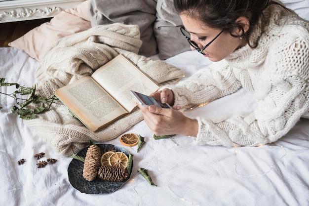 Joven mujer acostada en sábana con teléfono móvil