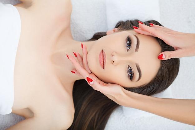 Joven mujer acostada en el salón de spa después del procedimiento de masaje corporal