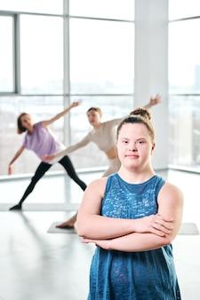Joven mujer activa con discapacidad en camiseta azul cruzando los brazos por el pecho mientras está de pie frente a la cámara sobre fondo de mujeres haciendo ejercicio