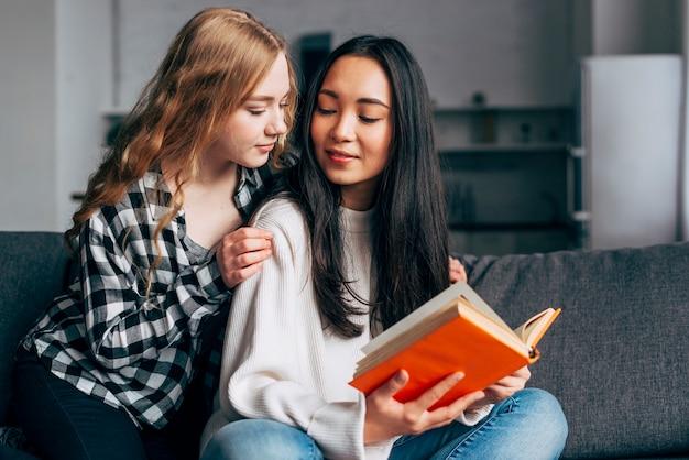 Joven mujer acurrucándose en novias con libro