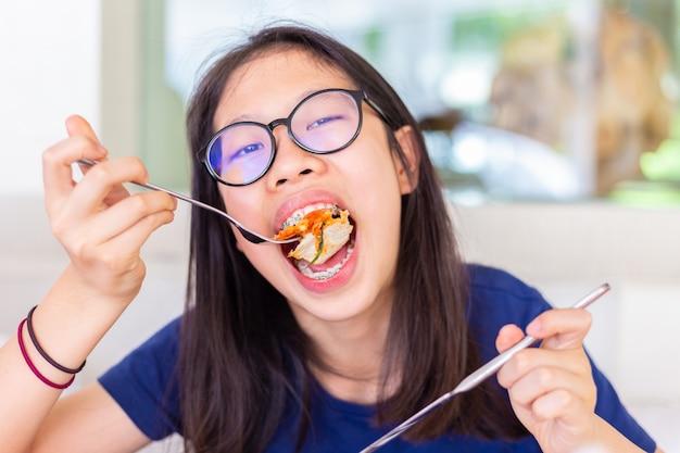Joven mujer adolescente con aparatos dentales comiendo y mordiendo su pizza