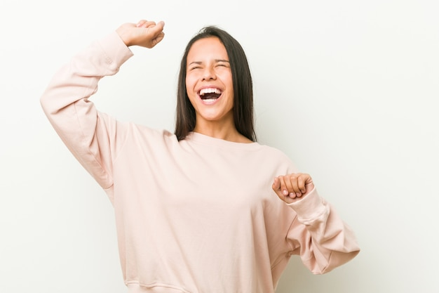 Joven mujer adolescente hispana linda celebrando un día especial, salta y levanta los brazos con energía.