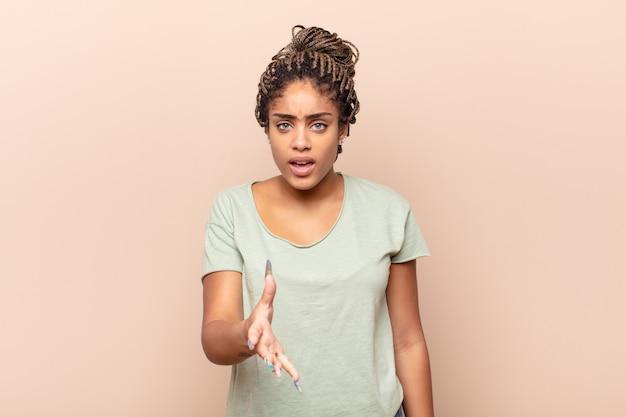 Joven mujer afro con aspecto enojado, molesto y frustrado gritando wtf o qué te pasa
