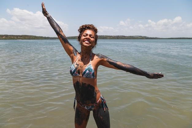 Joven mujer afro bañándose en arcilla natural en el río.