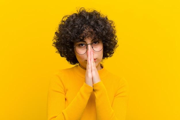 Joven mujer afro bonita que se siente preocupada, esperanzada y religiosa, rezando fielmente con las palmas presionadas, pidiendo perdón