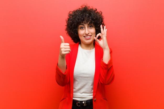 Joven mujer afro bonita se siente feliz, asombrada, satisfecha y sorprendida, mostrando gestos bien y pulgares arriba, sonriendo
