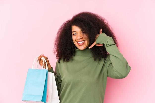 Joven mujer afro de compras aislado en rosa