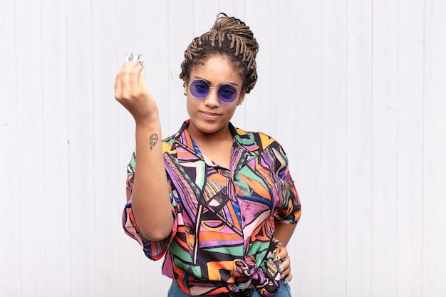 Joven mujer afro haciendo capice o gesto de dinero