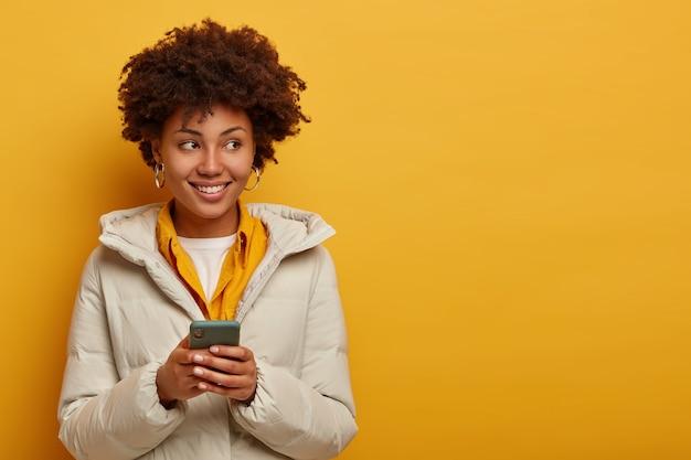 Joven mujer afro mira transmisión en vivo en línea, disfruta de mensajes agradables en el chat, posa sobre fondo amarillo