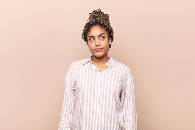 Joven mujer afro mirando perplejo y confundido, preguntándose o tratando de resolver un problema o pensando