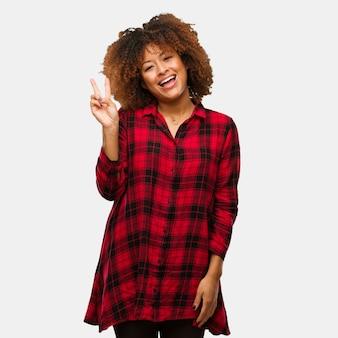 Joven mujer afro negra haciendo un gesto de victoria
