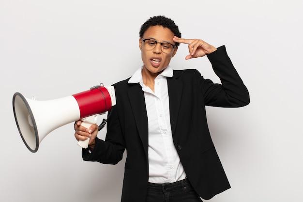 Joven mujer afro negra que se siente confundida y desconcertada, mostrando que está loco, loco o loco