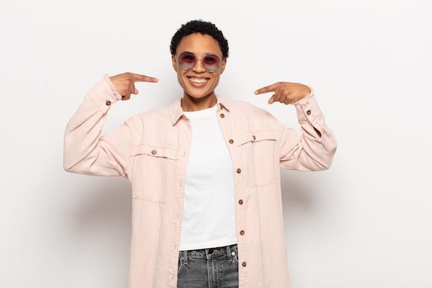 Joven mujer afro negra sonriendo con confianza apuntando a su propia sonrisa amplia, actitud positiva, relajada y satisfecha