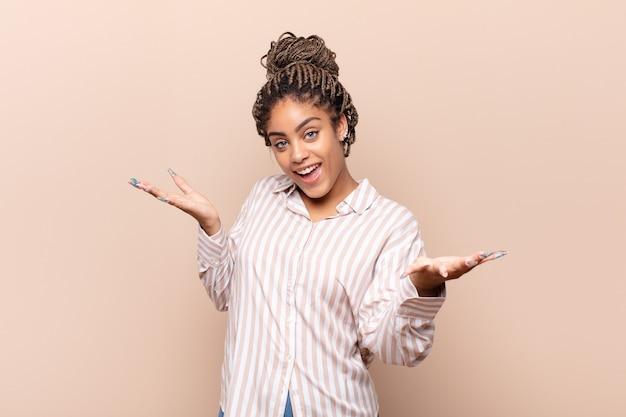 Joven mujer afro que parece feliz, arrogante, orgullosa y satisfecha de sí misma