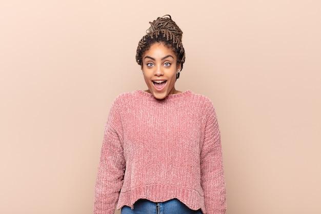 Joven mujer afro que se siente confundida y dudosa, preguntándose o tratando de elegir o tomar una decisión
