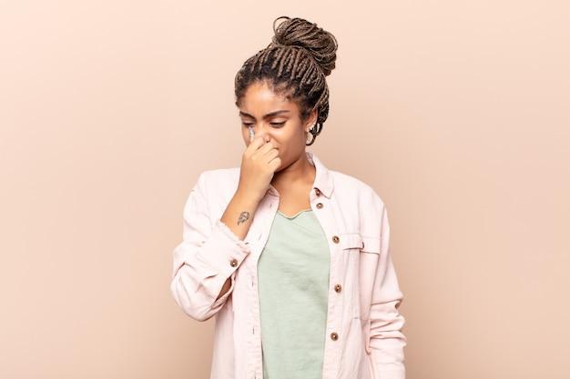 Joven mujer afro que se siente disgustada, tapándose la nariz para evitar oler un hedor desagradable y desagradable