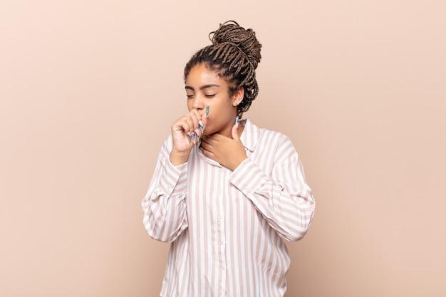 Joven mujer afro que se siente enferma con dolor de garganta y síntomas de gripe, tos con la boca cubierta
