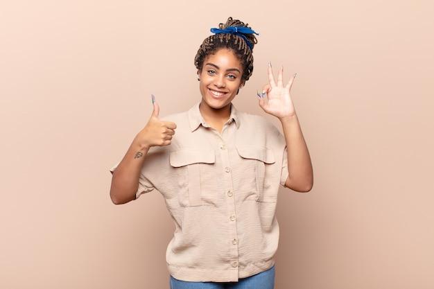 Joven mujer afro que se siente feliz, asombrada, satisfecha y sorprendida, mostrando gestos de aprobación y pulgar hacia arriba, sonriendo