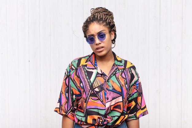 Joven mujer afro que se siente perpleja y confundida, con una expresión tonta y aturdida mirando algo inesperado