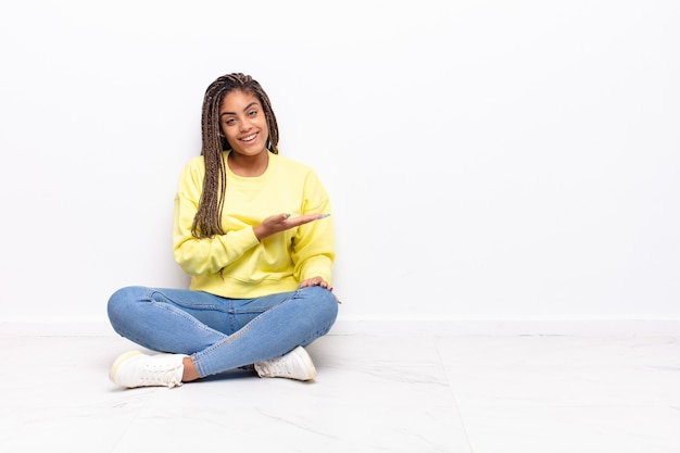 Joven mujer afro sonriendo alegremente, sintiéndose feliz y mostrando un concepto en el espacio de la copia con la palma de la mano