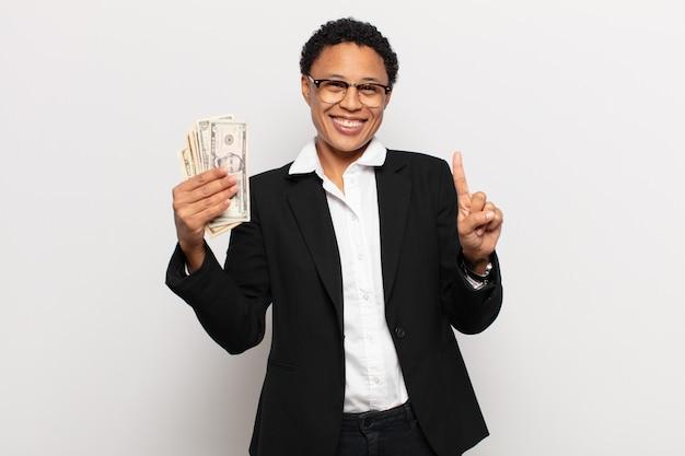 Joven mujer afro sonriendo con orgullo y confianza haciendo la pose número uno triunfalmente, sintiéndose como una líder