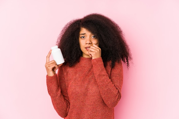 Joven mujer afro sosteniendo vitaminas