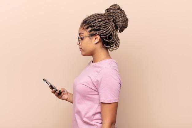Joven mujer afro en vista de perfil mirando