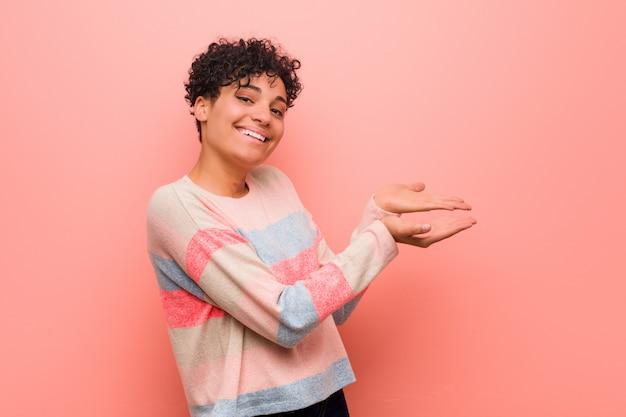 Joven mujer afroamericana adolescente mezclada con un espacio de copia en una palma.