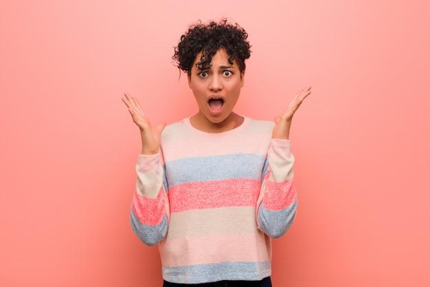 Joven mujer afroamericana adolescente mezclada sorprendida y conmocionada.
