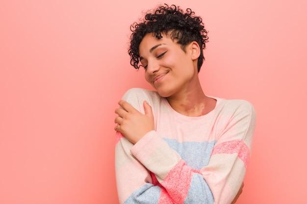 Joven mujer afroamericana adolescente mixta abrazos, sonriendo despreocupado y feliz.