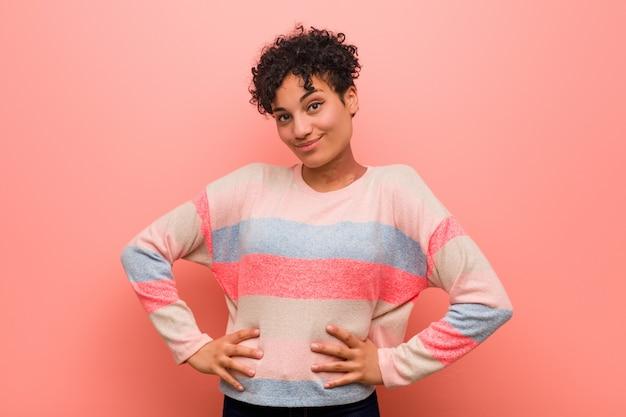 Joven mujer afroamericana adolescente mixta confía en mantener las manos en las caderas.