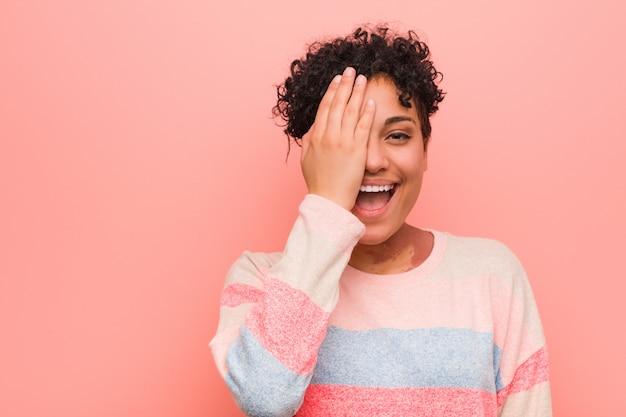 Joven mujer afroamericana adolescente mixta divirtiéndose cubriendo la mitad de la cara con la palma.