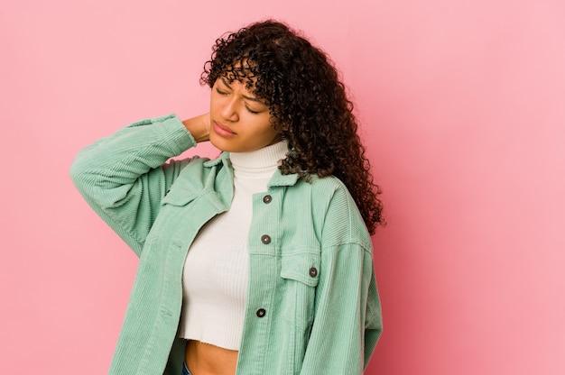 Joven mujer afroamericana afro aislada con dolor de cuello debido al estrés, masajeando y tocándolo con la mano.