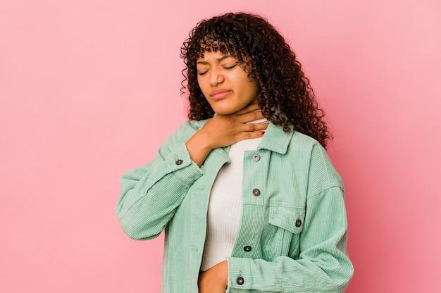 Joven mujer afroamericana afro aislada sufre dolor de garganta debido a un virus o infección.