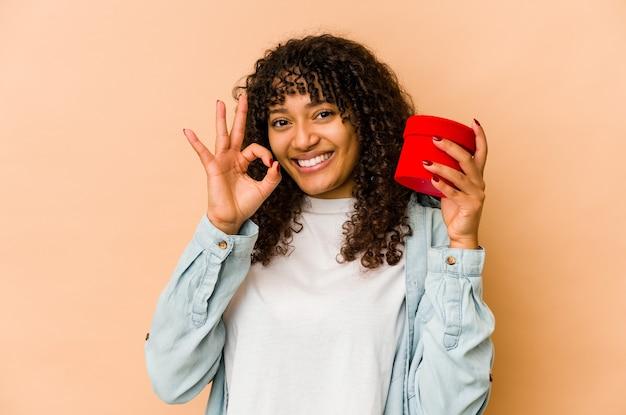 Joven mujer afroamericana afro sosteniendo un regalo de san valentín alegre y confiado mostrando gesto ok.