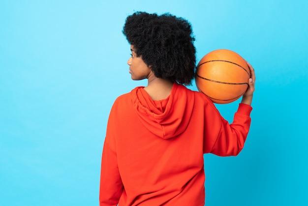Joven mujer afroamericana aislada en la pared azul jugando baloncesto en posición posterior