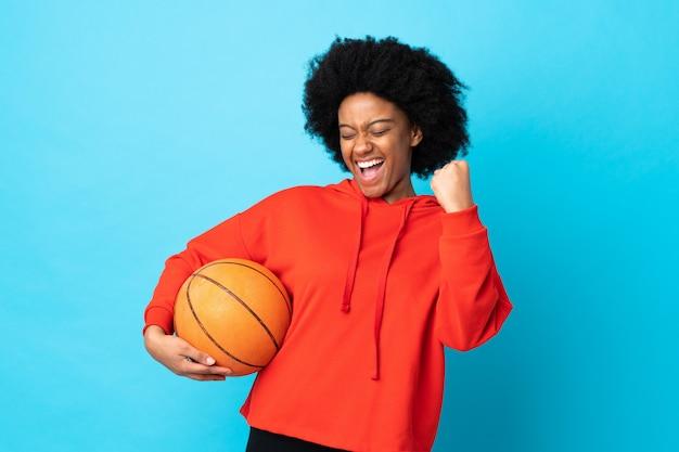 Joven mujer afroamericana aislada en la pared azul jugando baloncesto