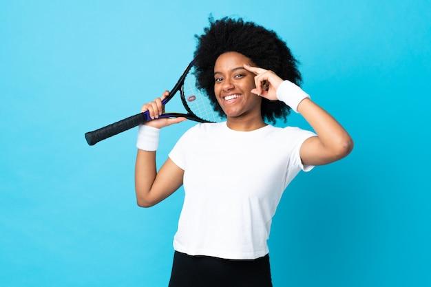 Joven mujer afroamericana aislada en la pared azul jugando tenis