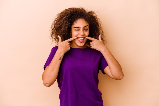 Joven mujer afroamericana aislada en la pared beige sonríe, señalando con el dedo a la boca
