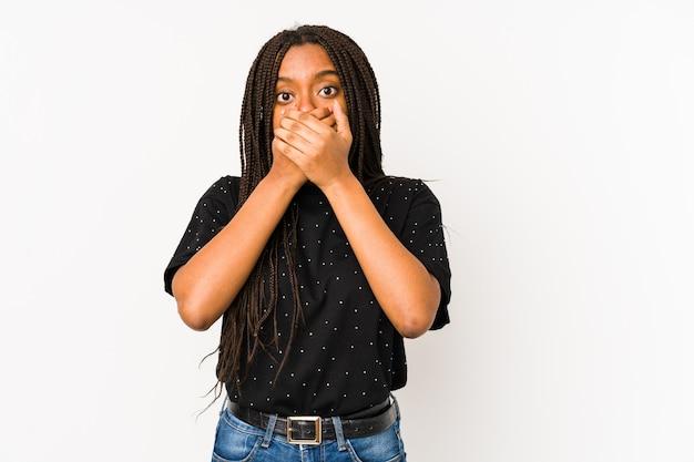 Joven mujer afroamericana aislada en la pared blanca sorprendido cubriendo la boca con las manos.