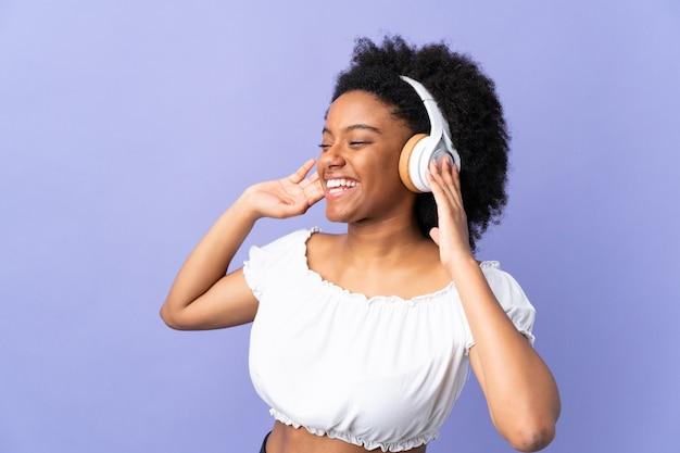 Joven mujer afroamericana aislada en la pared púrpura escuchando música y cantando