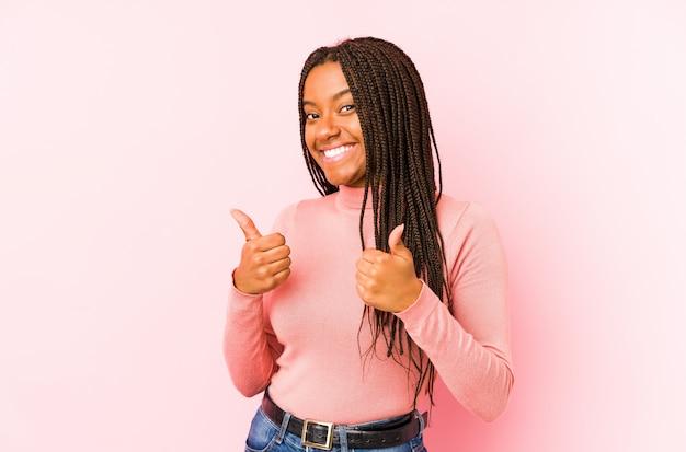 Joven mujer afroamericana aislada en una pared rosa levantando ambos pulgares, sonriente y confiado.