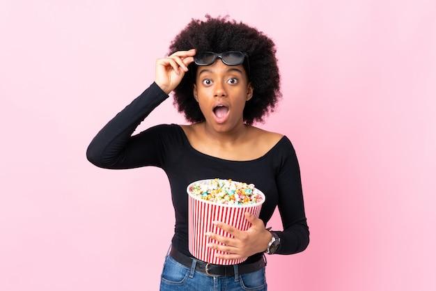 Joven mujer afroamericana aislada en la pared rosa sorprendida con gafas 3d y sosteniendo un gran cubo de palomitas de maíz