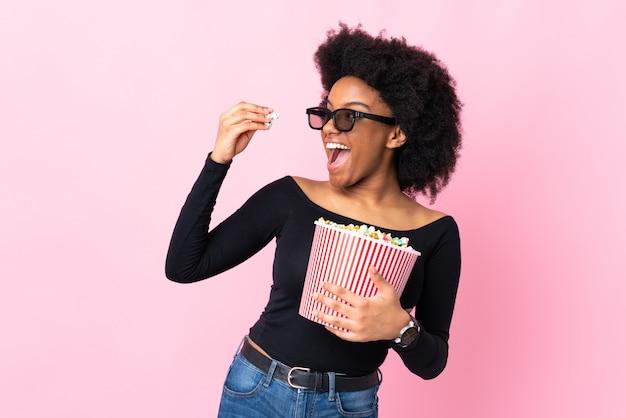 Joven mujer afroamericana aislada en rosa con gafas 3d y sosteniendo un gran cubo de palomitas de maíz