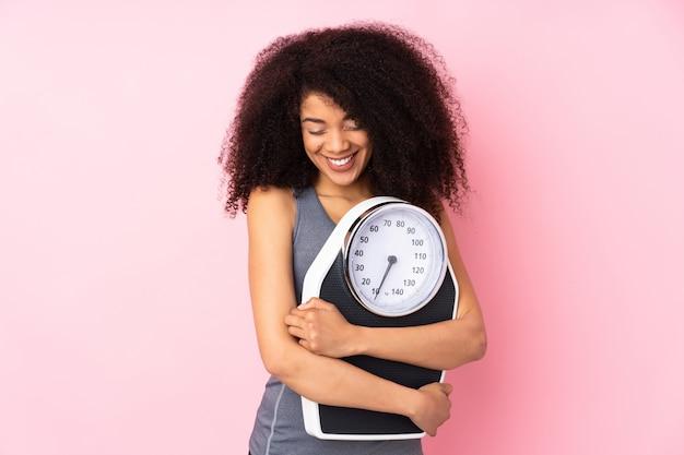 Joven mujer afroamericana aislada en rosa con máquina de pesaje