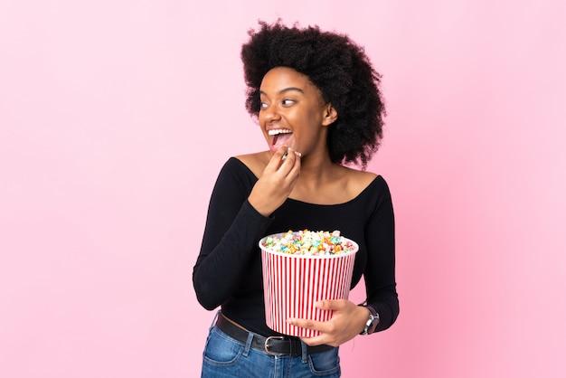 Joven mujer afroamericana aislada en rosa sosteniendo un gran cubo de palomitas de maíz