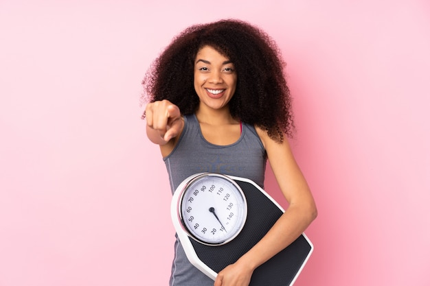 Joven mujer afroamericana aislada en rosa sosteniendo una máquina de pesaje y apuntando hacia el frente