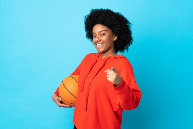 Joven mujer afroamericana aislada sobre fondo azul jugando baloncesto y apuntando hacia el frente