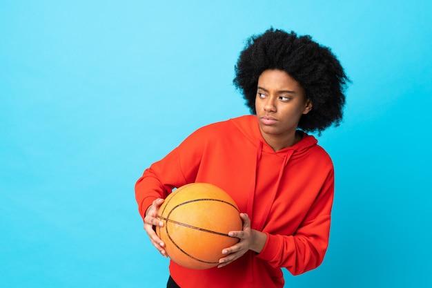 Joven mujer afroamericana aislada sobre fondo azul jugando baloncesto