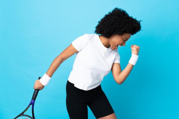 Joven mujer afroamericana aislada sobre fondo azul jugando tenis y celebrando una victoria